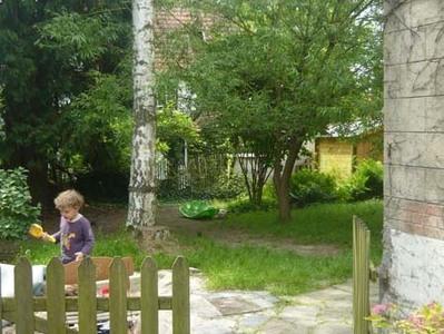 Petite barrière menant au jardin derrière la maison et au bac à sable.